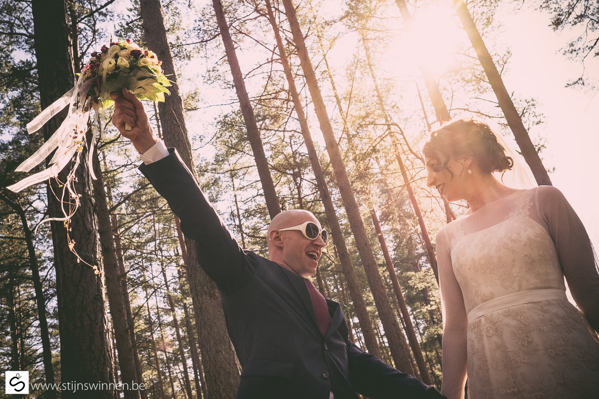 Man holding up bouquet. Sun in the background